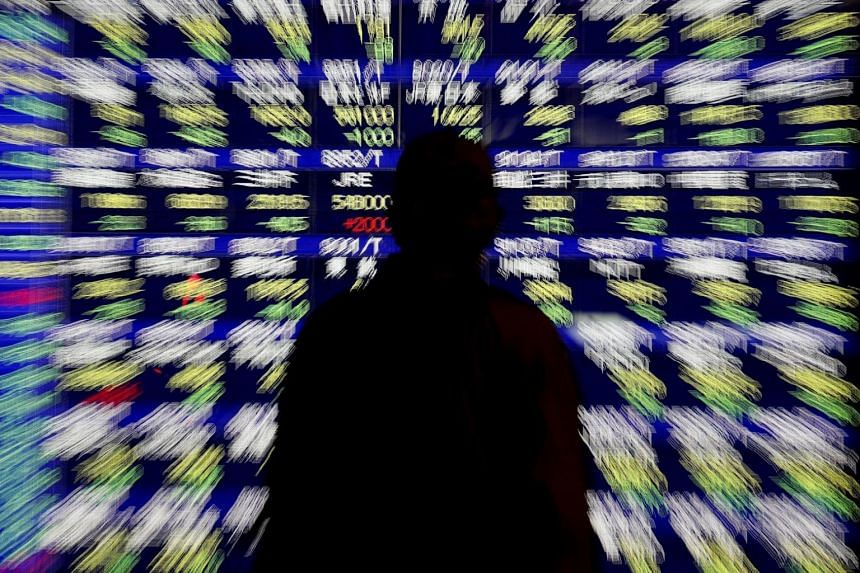 A pedestrian looking at the Nikkei Stock Average index information on a display at a securities company office in Tokyo.