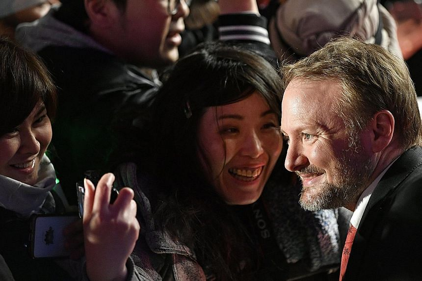 Star Wars: The Last Jedi's director Rian Johnson with fans during the film's red-carpet event in Tokyo, Japan, earlier this month. Actress Carrie Fisher, who died in December last year, stars as General Leia in The Last Jedi.