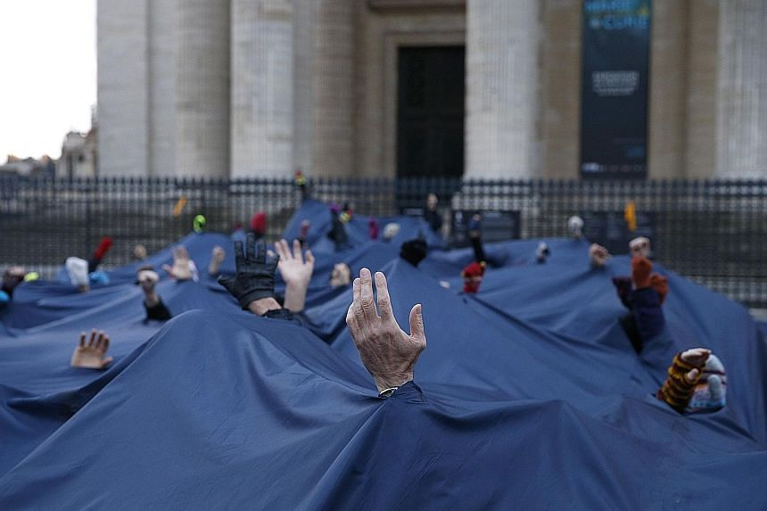 A demonstration outside the Pantheon in Paris yesterday, on the sidelines of the One Planet summit. More than 200 institutional investors with $35 trillion in assets under management said they would step up pressure on the world's biggest corporate g