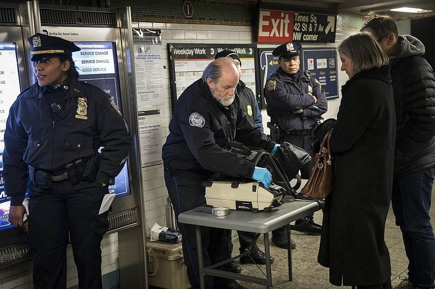 Left: Subway bombing suspect Akayed Ullah, who suffered burns to his body and hands, being taken to hospital in an ambulance after the attack on Monday. Below: Transportation Security Administration staff and police officers checking the bags of pass