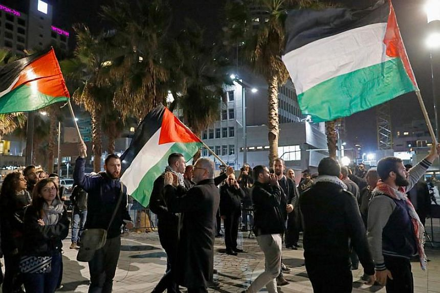 Arab-Israeli protesters waving Palestinian flags during a demonstration in front the American Embassy in the Israeli city of Tel Aviv on Dec 12, 2017.