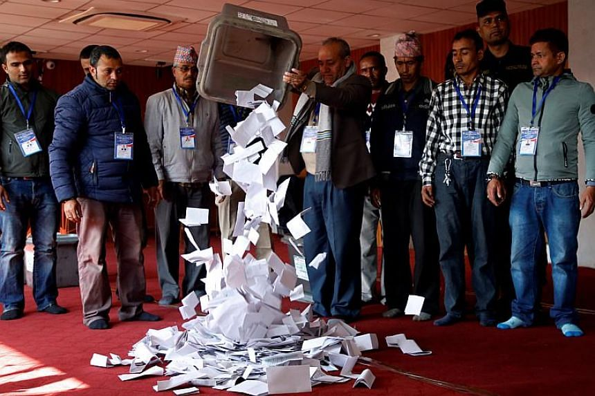An official from the election commission pours the ballot papers from the box, a day after the parliamentary and provincial elections in Kathmandu, Nepal on Dec 8, 2017.