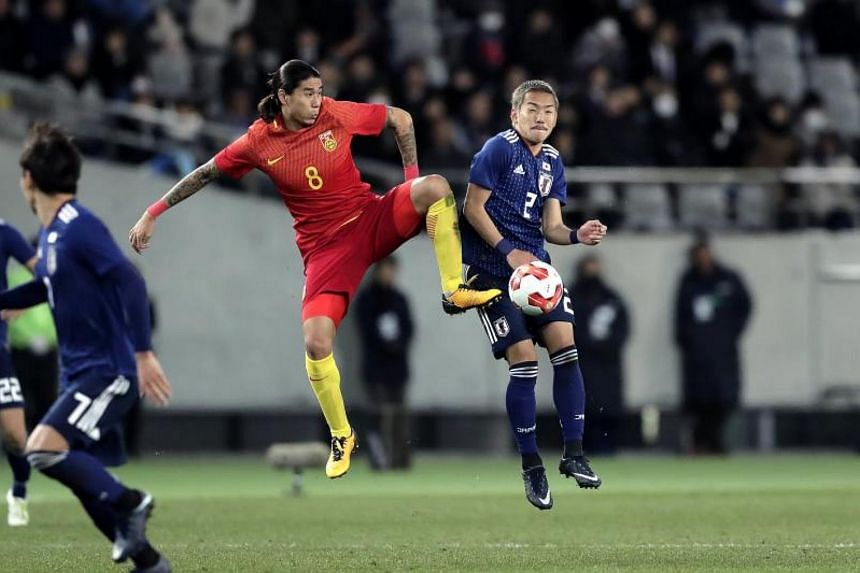 China's midfielder Zhao Yuhao (left) and Japan's midfielder Yosuke Ideguchi (right) in action during the East Asian Football Federation (EAFF) E-1 Football Championship match between Japan and China in Tokyo, Japan on Dec 12, 2017.