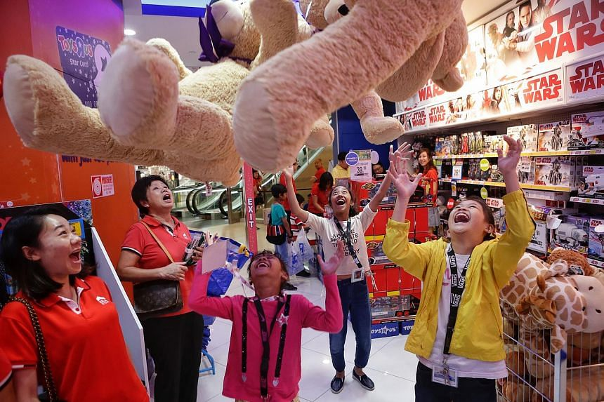 Nur Qanitah Husna Md Saad (centre), her sister Nur Karimah A'Lawiyyah (second left) and Karimah's friend Loo Pei Lin (right) tossing giant teddy bears during a shopping trip to Toys 'R' Us at Parkway Parade on Dec 13, 2017.