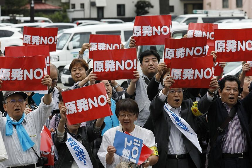 """Protesters holding up placards saying """"No nuclear power plant"""" during a demonstration in Fukushima on Oct 10, 2017. Hiroshima's High Court reversed a ruling allowing the Ikata No.3 plant, located in Nishiuwa, Ehime prefecture, to operate, on Dec 13,"""