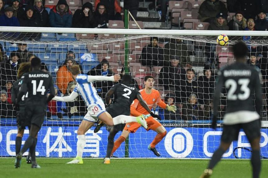 Huddersfield Town's Belgian striker Laurent Depoitre (second, left) heads the ball to score past Chelsea's Belgian goalkeeper Thibaut Courtois during the match at the John Smith's stadium in Huddersfield, northern England on Dec 12.
