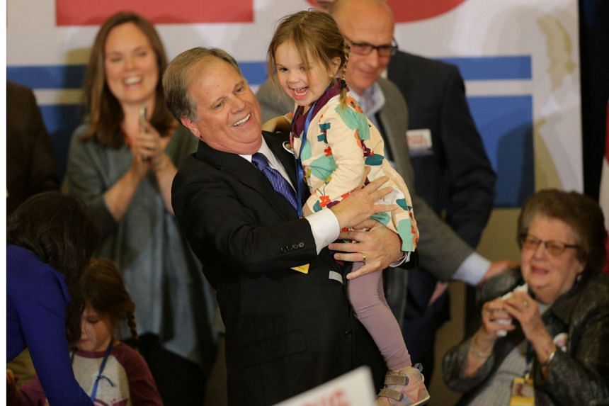 Democratic Alabama US Senate candidate Doug Jones holds his granddaughter as he celebrates with supporters at the election night party in Birmingham, Alabama, on Dec 12, 2017.