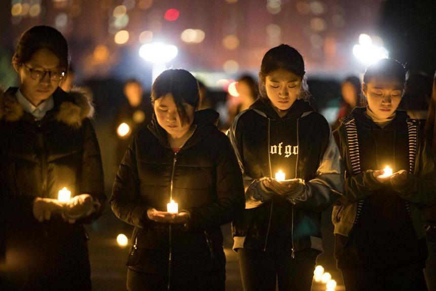 Students holding candles at Nanjing Normal University during a memorial ceremony ahead of China's National Memorial Day for Nanjing massacre victims, on Dec 11.