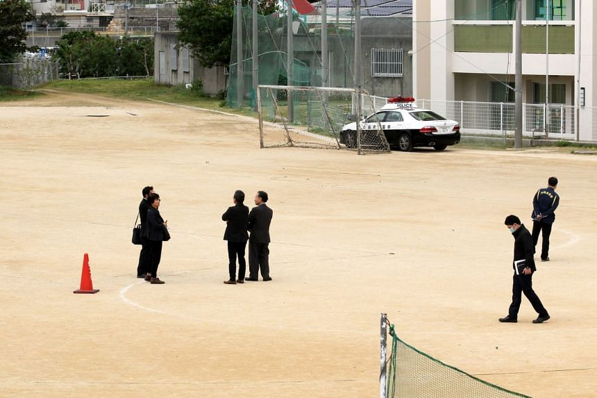 Police investigators inspect the ground where the window of a CH-53E helicopter fell onto the sports ground at Daini Futenma Elementary School.