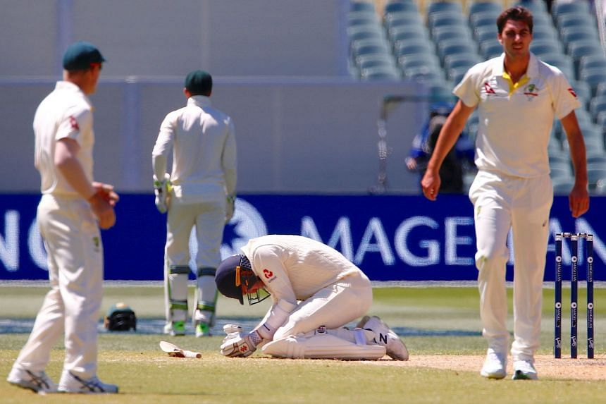 England's Craig Overton reacts after being hit by a delivery from Australia's Pat Cummins during the fifth day of the second Ashes cricket test match in Adelaide, Australia, on Dec 6, 2017.