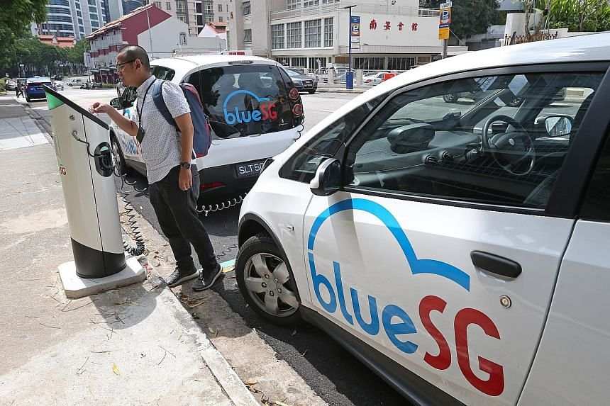 From left: The reporter at one of BlueSG's charging locations in Mohamed Sultan Road and driving the electric car, which is like being at the wheel of a petrol-driven one. The app shows the cost of the journey.