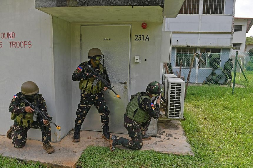 "It was mission accomplished for 23 elite troops from the Philippines after they ""stormed and captured"" a number of buildings in their final exercise at the Murai Urban Training Facility in Lim Chu Kang yesterday. 	The Philippine soldiers are in Singa"