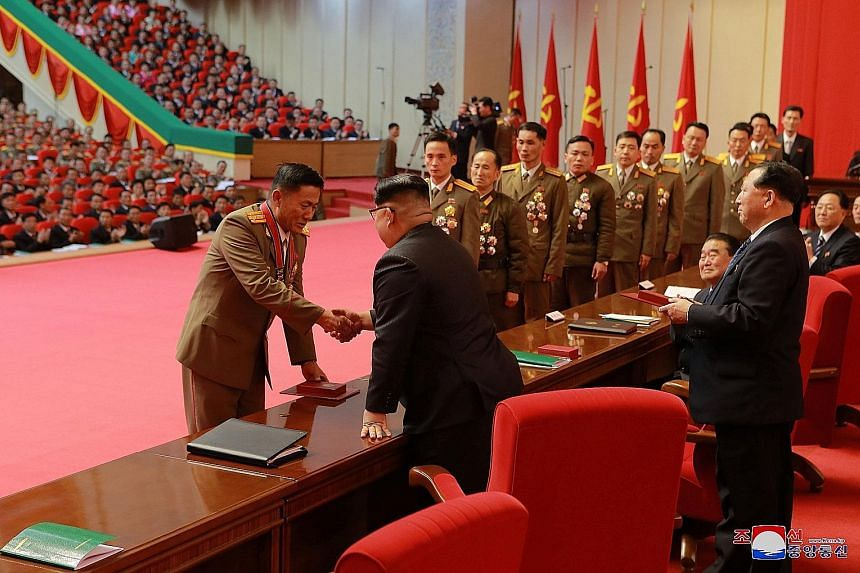 Mr Kim Jong Un presenting awards to scientists, technicians and workers who contributed to the successful launch of intercontinental ballistic rockets, in a photo released by North Korea's central news agency KCNA. The presentation took place at a ra