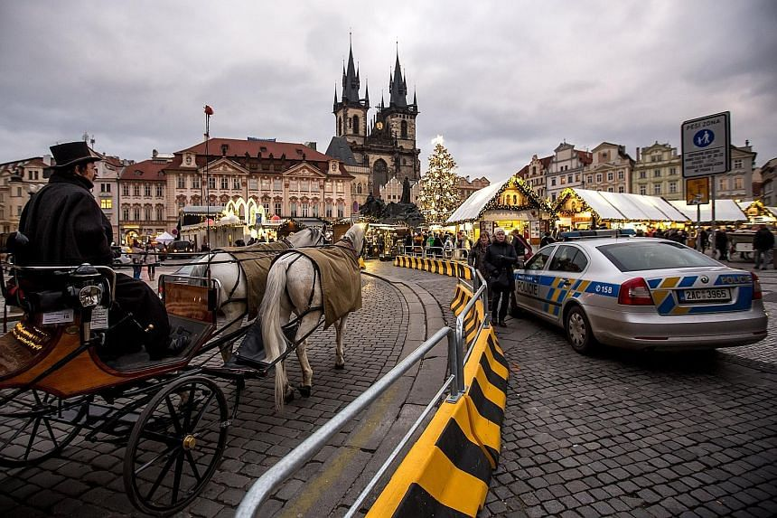 A police patrol car and roadblocks put up to prevent vehicle attacks at a Christmas market in Prague's Old Town Square earlier this month. Such security measures are being taken across Europe this year, with the authorities mindful that militants car