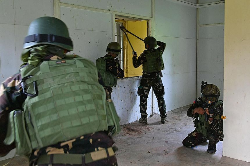 The Philippine soldiers forming up before an assault on the buildings. The two-hour-long exercise in Lim Chu Kang yesterday was the culmination of a two-week exchange programme between the Philippine and Singapore armed forces.