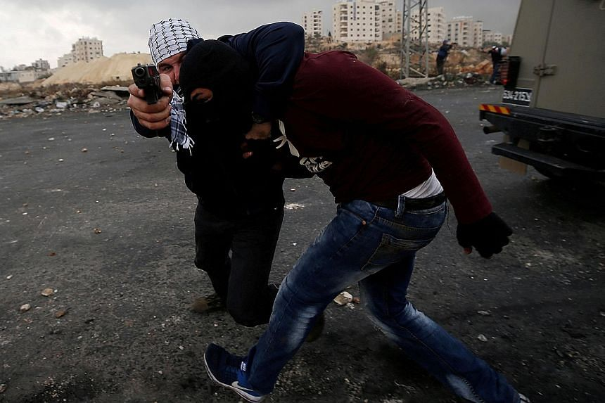 An undercover Israeli security officer detaining a Palestinian during clashes at a rally yesterday against the US decision on Jerusalem, near the Jewish settlement of Beit El, close to Ramallah in the West Bank.