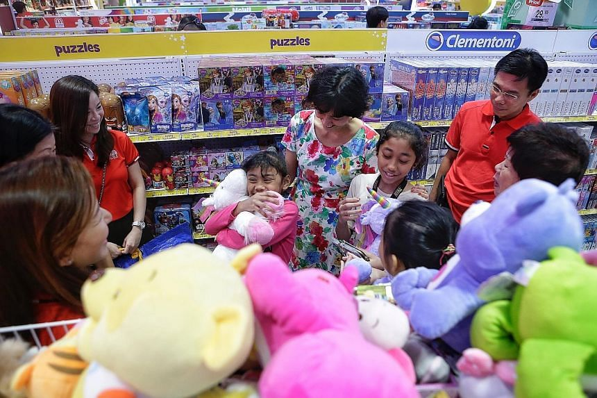 Sisters Nur Qanitah Husna Md Saad, seven, and Nur Kamirah A'Lawiyyah, 11, were among 50 children who picked out new toys yesterday at Toys 'R' Us in Parkway Parade. Kamirah chose a giant teddy bear and two keychains for herself and her mother, while