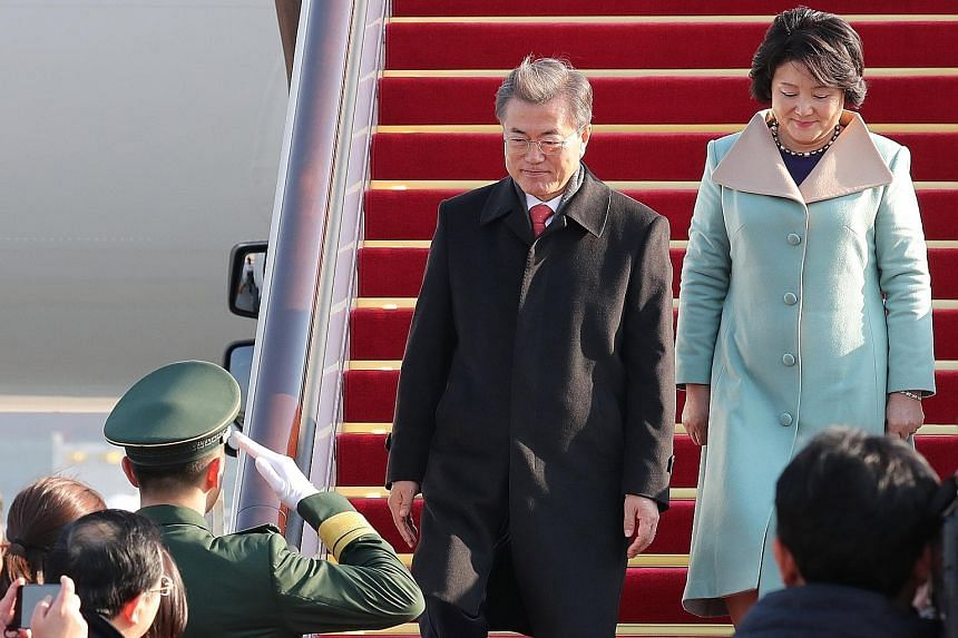 South Korean President Moon Jae In and his wife Kim Jung Sook arriving in Beijing yesterday. Mr Moon will hold a bilateral summit with President Xi Jinping, attend business forums and travel to Chongqing over four days.