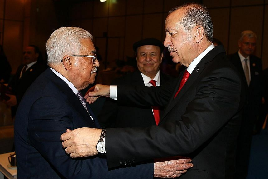 """Turkish President Recep Tayyip Erdogan (far right) greeting Palestinian President Mahmoud Abbas yesterday during the OIC summit in Istanbul. In a communique, the OIC said the US decision on Jerusalem was """"null and void legally"""", and """"a deliberate und"""