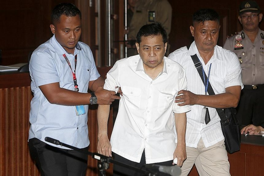 Setya Novanto being escorted by Corruption Eradication Commission officers during his first trial at the Central Jakarta district court yesterday. Doctors found him fit to stand trial, but he refused to answer questions and confirm details like his n