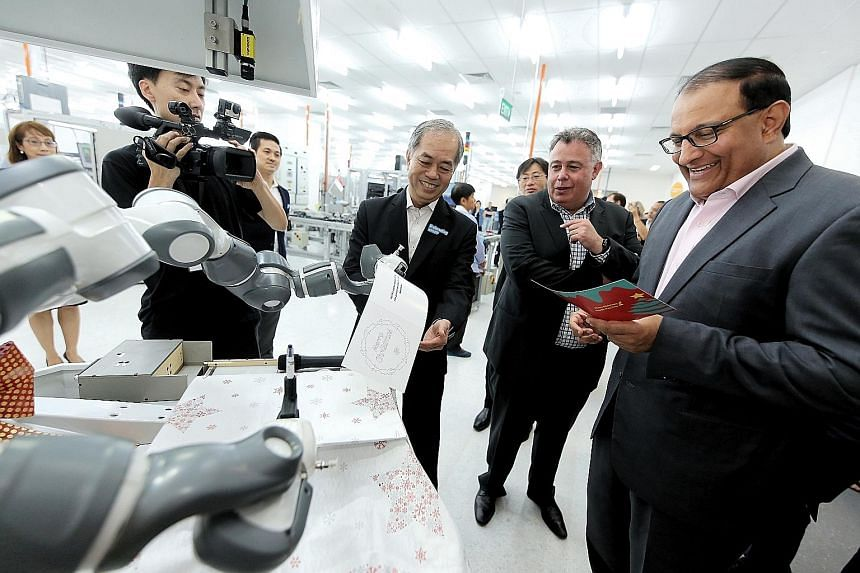 Minister S. Iswaran receiving a card with greetings written by a robotic arm at HP's first Smart Manufacturing Applications and Research Centre. With him are Mr Dominic Chew, HP director of operations, supplies operations, and Mr Dion Weisler, HP pre