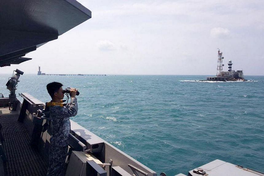 An RSS Sovereignty crew member scanning the horizon for the capsized fishing boat.