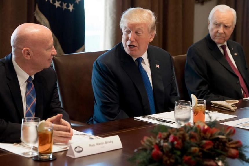 US President Donald Trump speaks about tax reform legislation during a lunch with lawmakers including Senator Orrin Hatch (right), Republican of Utah, and Representative Kevin Brady (left), Republican of Texas, in the Cabinet Room at the White House