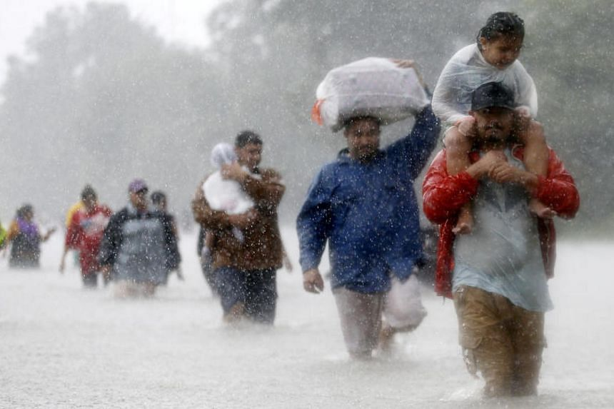 Residents wade through flood waters from Tropical Storm Harvey in Beaumont Place, Houston, Texas on Aug 28, 2017.