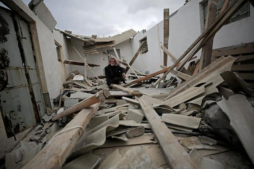 A Palestinian man sits on the ruble of his house, which was destroyed by Israeli air strikes in Khan Younis town, Gaza Strip, on Dec 13, 2017.