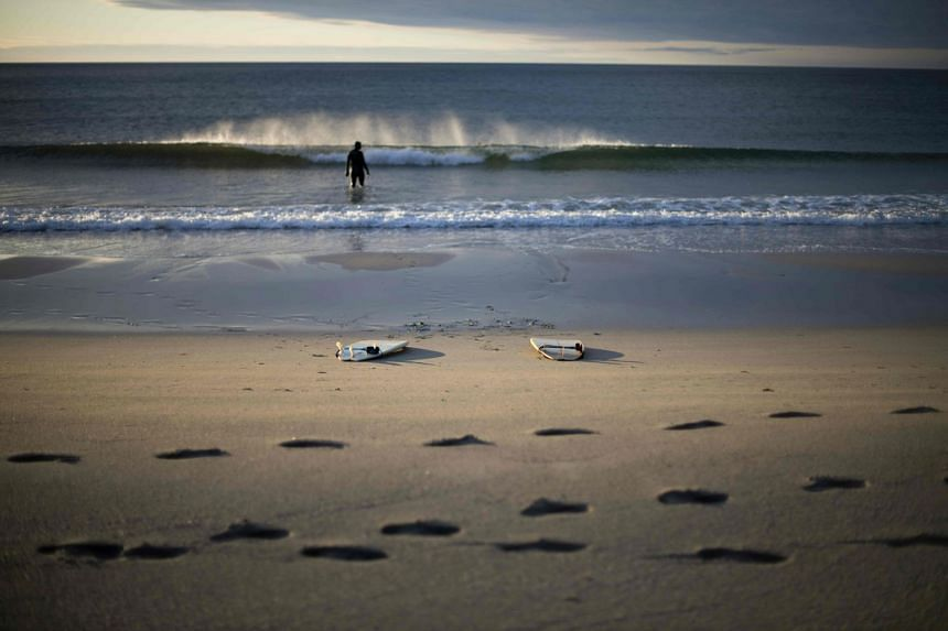 A man walks in the water after a surf session in Unstad's bay in the arctic circle, on Sept 21, 2017.