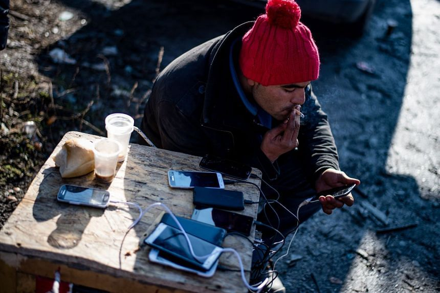 A migrant charges his mobile phone in an abandoned printing factory in the western Serbian town of Sid, Dec 7, 2017.