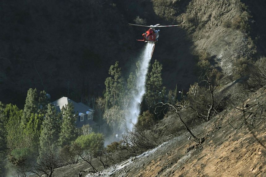 A helicopter does a water drop beside a luxury house after the Skirball wildfire swept through the exclusive enclave of Bel-Air, California on Dec 7, 2017.