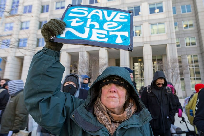 A woman holds a 'Save the Net' protest sign during a demonstration against the proposed repeal of net neutrality outside the Federal Communications Commission headquarters in Washington, DC on Dec 13, 2017.