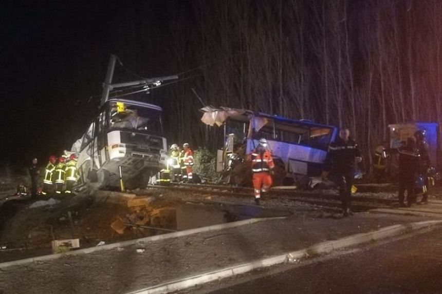 Emergency personnel at the crash site of a school bus with a train in Southern France.