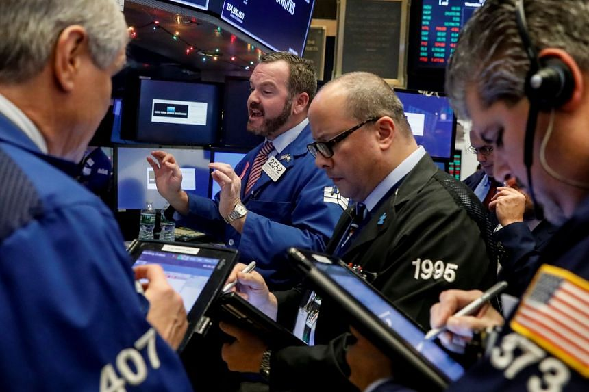 Traders work at the post where Walt Disney stock is traded on the floor of the New York Stock Exchange.