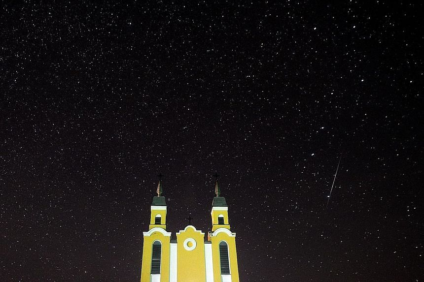 "It was like a magical scene right out of a story book as a meteor or shooting star streaked across the sky above a church in Krevo village, north-west of Minsk, Belarus, yesterday during the annual Geminid meteor shower. Astronomers had expected a ""s"