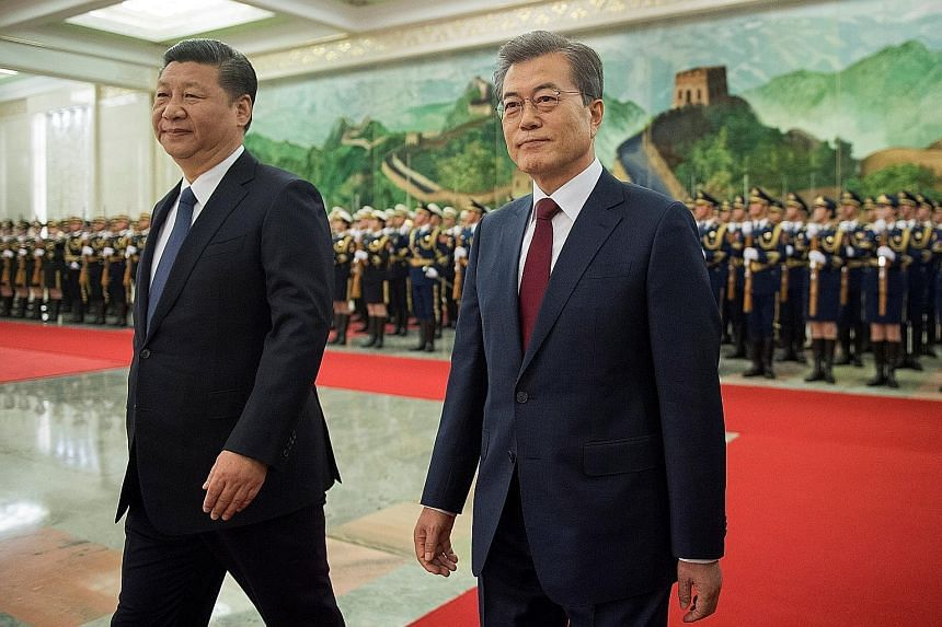 Chinese President Xi Jinping (left) and South Korean President Moon Jae In reviewing the Chinese honour guard during a welcome ceremony at the Great Hall of the People in Beijing yesterday.