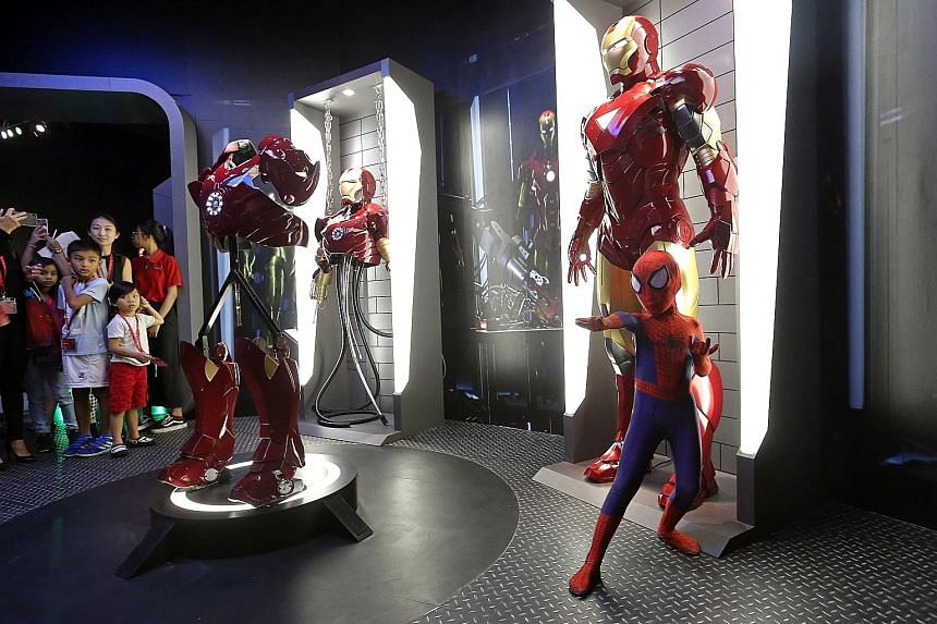 Leroy Teo, eight, dressed as Spider-Man, poses next to Iron Man at the Marvel exhibits at Madame Tussauds Singapore on Sentosa.