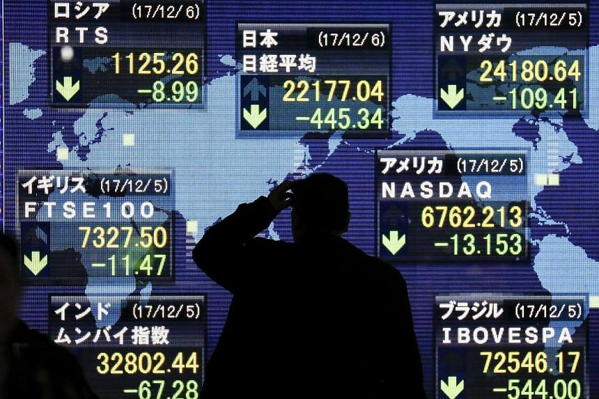 A man watches closing information of the Nikkei Stock Average and global stock markets shown on a display at a securities company office in Tokyo, Japan on Dec 6, 2017.