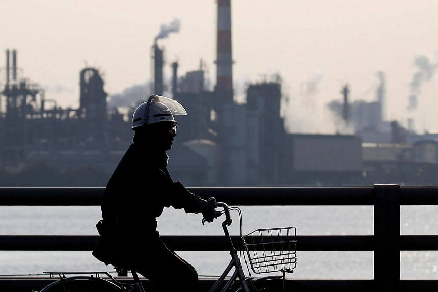 A worker cycles near a factory at the Keihin industrial zone in Kawasaki, Japan, on Nov 15.