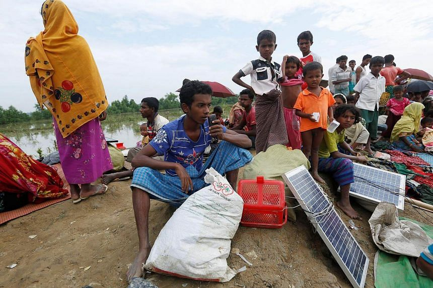A Rohingya refugee charges his phone with a solar panel as he waits to be taken to a refugee camp, on Nov 2, 2017.