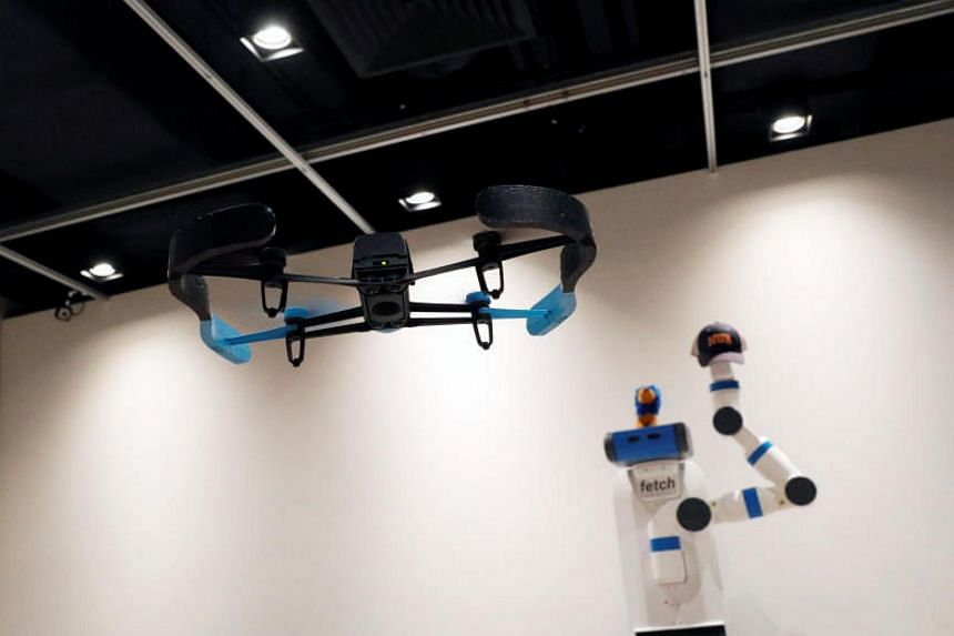 A drone taking photos of a robot during a demonstration of Xpose, an interactive drone photo-taking system, at the NUS School of Computing faculty premises in Singapore on Nov 27, 2017.