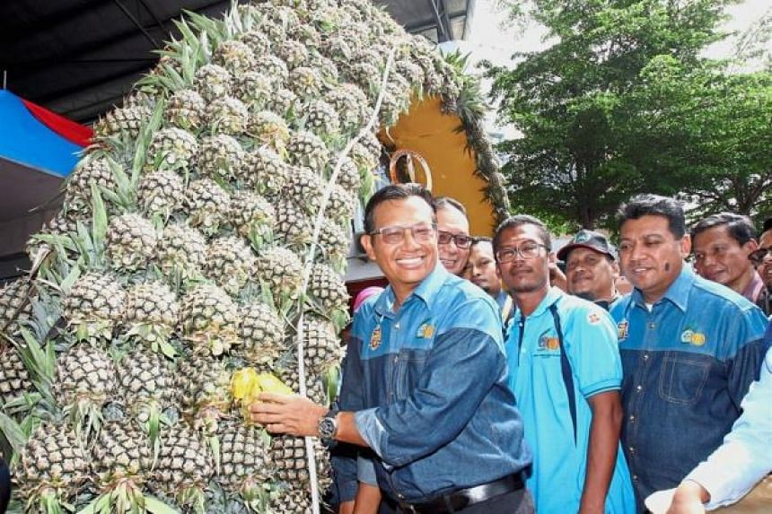 Malaysia's Agriculture and Agro-based Industry Minister Datuk Seri Ahmad Shabery Cheek putting a pineapple on an arch at the launch of MPIB's 60th Anniversary Pineapple Fiesta.
