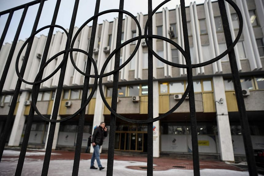 A man talking on the phone in front of the headquarters of the Russian Olympic Committee in Moscow.