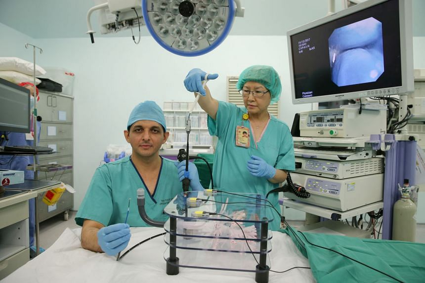 """Dr Akash Verma and Senior Staff Nurse Chin Mee Choo with equipment for navigational bronchoscopy. In the procedure, a three-dimensional """"road map"""" is created and it shows several routes a doctor can take to insert a tube into the lung to the target s"""