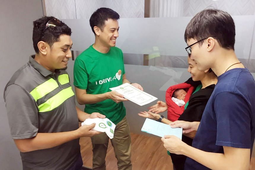 Grab driver Mohammad Fazli Omar and GrabCar Singapore head Andrew Chan presenting Mr Reuben Chow and Madam Cindy Lim with a Grab voucher worth $8,000, and a special Grab garment for newborn baby Elora-Fae.
