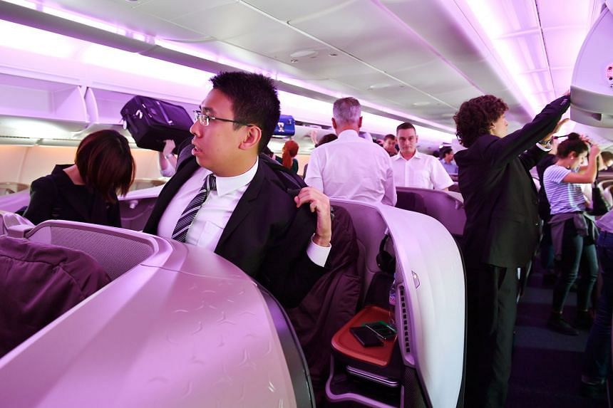 Changes have been made in business class, such as more stowage space and a mechanism that turns the seat into a full-flat bed with the push of a button. Passengers in business class getting ready to get off the plane after the Singapore Airlines A-38