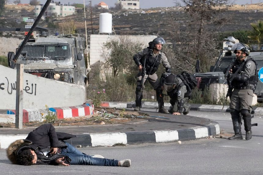 A Palestinian man clutches his stomach after he was shot by Israeli soldiers, in reaction to his attack on a soldier.