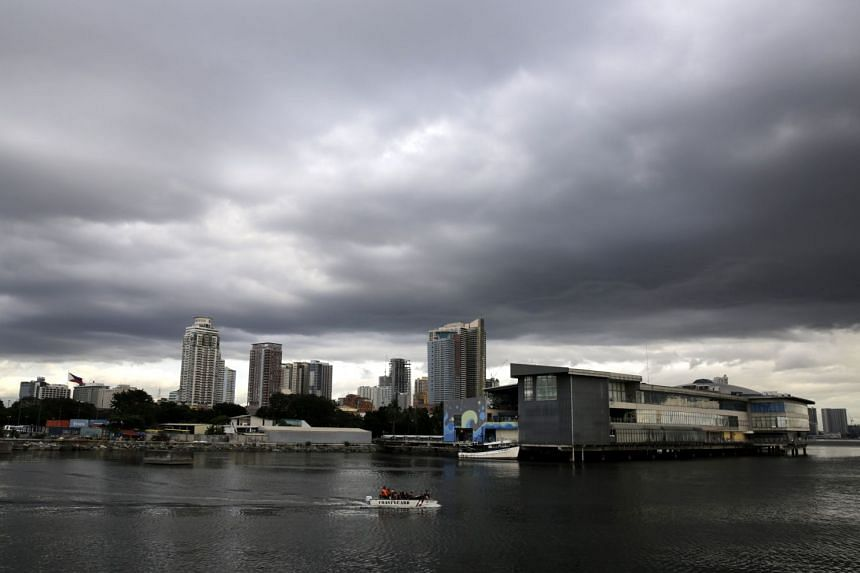 Philippine Coastguard personnel patrol on a boat as thick cloud looms over Manila on Dec 14, 2017.