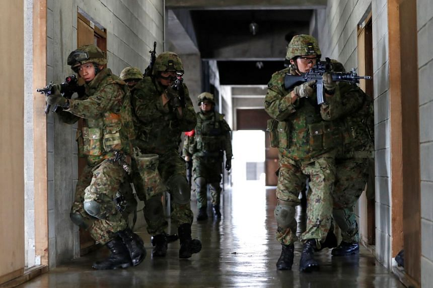 Japan Ground Self-Defence Force members taking part in an urban warfare drill during a joint military exercise with the US Army.